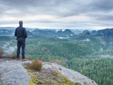Man stop for watching misty landscape. Moment on the edge