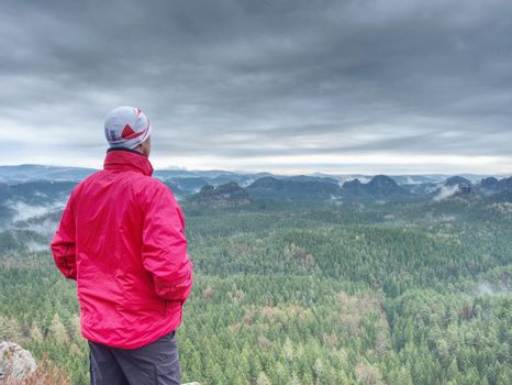 Sportsman in red with hands in pockets stand on the peak