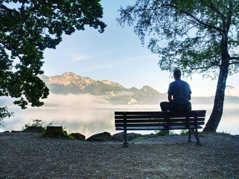Man sit lone on bench in park next lake. Mountain range