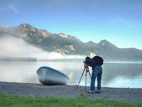 Man hiker is taking photo of ship at mountain lake shore.
