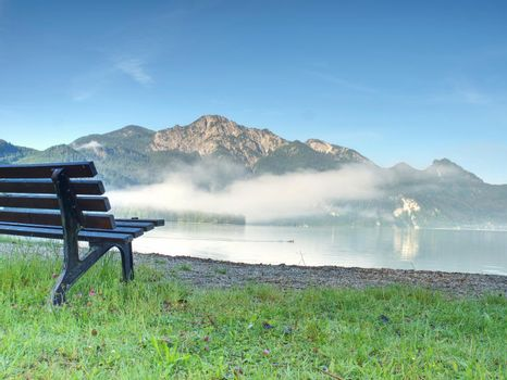 Lake landscape with a bench in the foreground ready to relax.