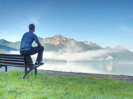 Man sit on wooden bench at coast of lake bellow blue mountains