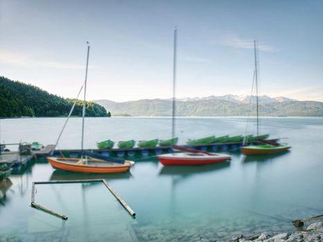 Sports boats, blue green mountain lake, windless day.