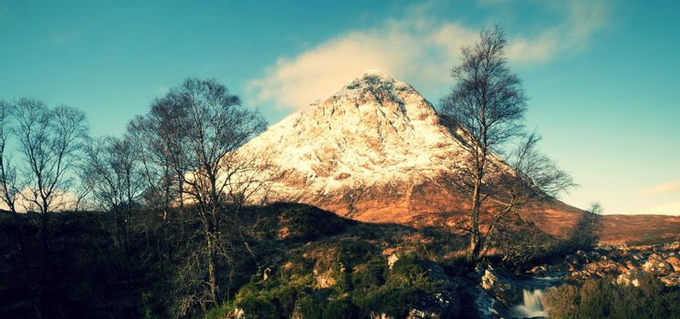 Higland in Scotland. Marvelous day  at frozen river Coupall at delta to river Etive. Snowy cone of mountain