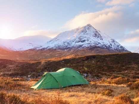 Green touristic tent on meadow at river below snowy cone of mountain Stob Dearg 1021 metres high