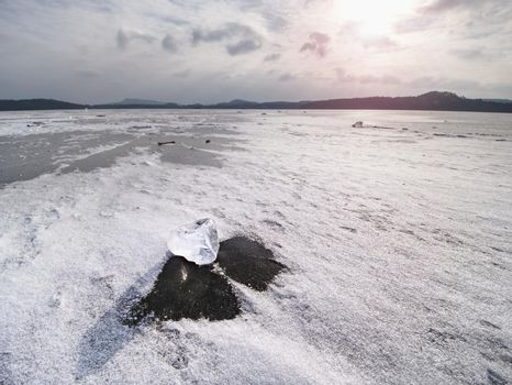 Drifting piece of iceberg and sun glaring on thick ice cover.