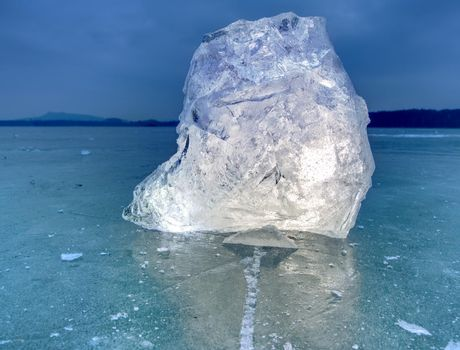 Arctic ice. A large piece of natural ice on a green blue flat ice of frozen lake