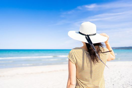 Tropical sea travel ADV banner style: unrecognizable woman holding white large hat with a hand looking to the blue ocean water standing on white silked sand under blue sky. Escape from everyday life