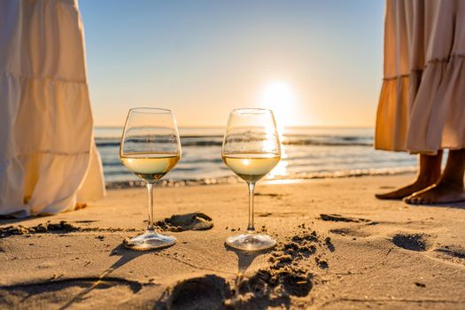 Sunset or sunrise beach party scene with two unrecognizable multiracial boho girls wearing long white dress barefoot on the ocean beach sand. Wine glasses on the ground with sun reflections effect