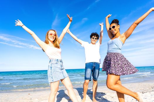 Three very happy friends having fun at the beach posing laughing looking at camera for a portrait with raised arms. Gen z multiracial carefree people in tropical beach with white sand and blue sky