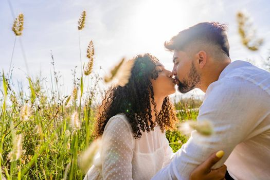Romance scene of mixed-race couple in love kissing in backlight effect among flowers and high grass with flare and reflection sun effect at sunset or sunrise. Bearded macho young man flirting