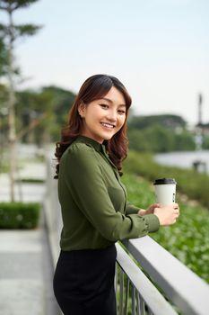 Pretty woman enjoying hot beverage in park