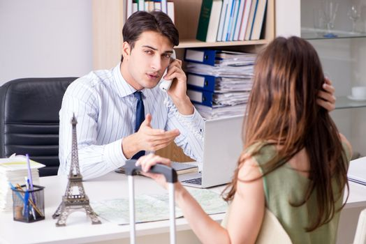 Male travel agent with customer in agency