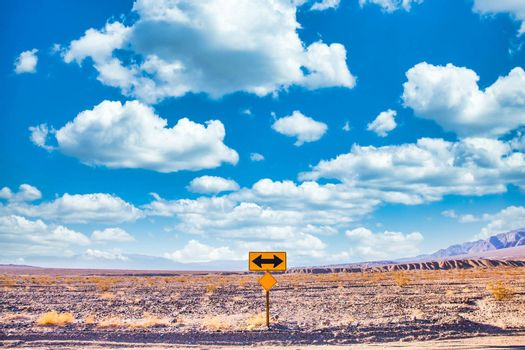 Directional sign in the desert with scenic blue sky and wide horizon. Concept for trip, freedom and transportation.