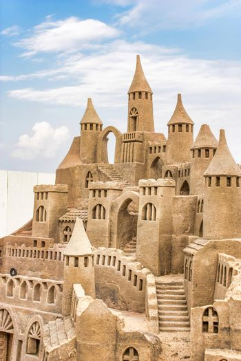 Sandcastle during a sunny day with blue sky background. Concept for summer, vacation and fun.