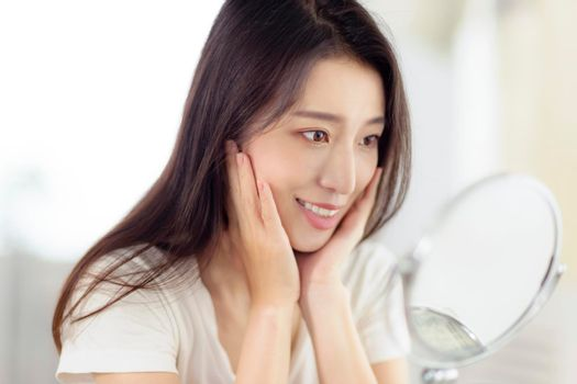 Asian young woman looking at her face in mirror