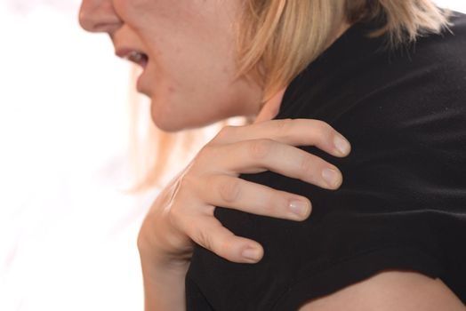 woman with pain in the shoulder holding the painful area