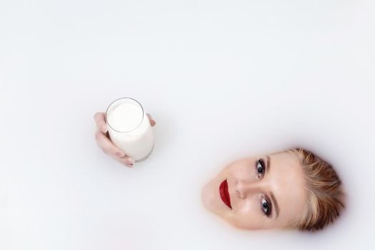 Attractive young woman with red lips lying in milk spa holding a glass of milk