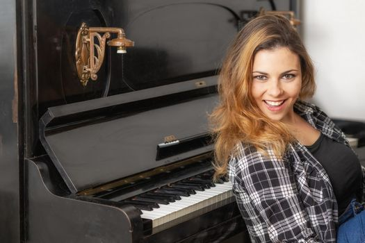 Portrait of attractive young woman posing at the piano.
