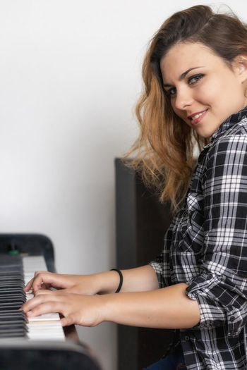 Portrait of beautiful young woman is playing the piano
