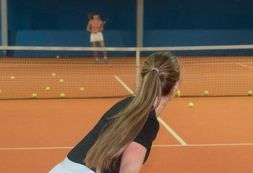 playing a tennis match in a tennis hall, indoor sports