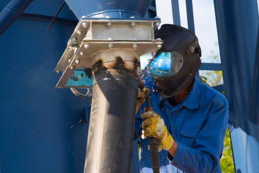a metal worker is welding a pipe in protective clothing