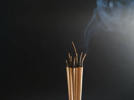 Burning incense white smoke black background used as a worship background image a sacred object of Buddhist beliefs focus on the smoke