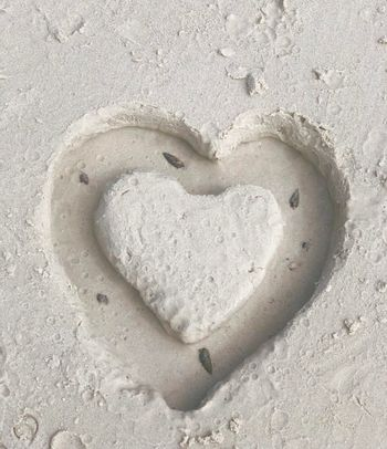 Top corner close-up of hand-drawn abstract heart on the beach, feeling, love concept.
