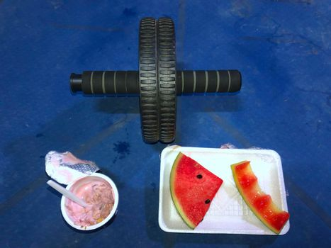 Yogurt and watermelon Upper-specific exercise rolling wheel blue yoga mat sectional exercise concept And healthy eating.