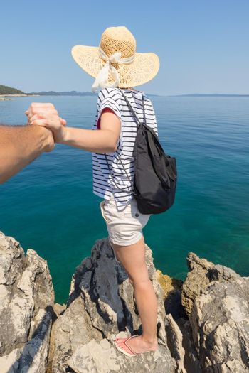 Woman traveler wearing straw summer hat and backpack, standing at edge of the rocky cliff, holding hand of her partner, looking at big blue sea and islands in on the horizon.