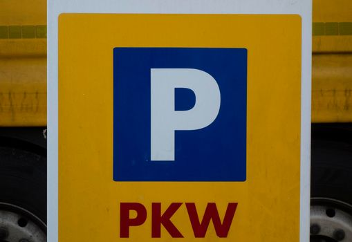 a blue parking lot road sign with a white P letter
