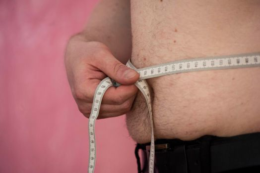 overweight man showing his belly, fat as a risk to health
