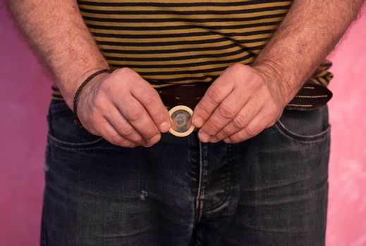 holding a condom in the hand, contraceptive and prevention against sexual transmitted disease