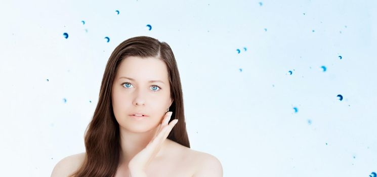 Rejuvenation skincare and beauty ad, beauty face portrait of young woman with healthy clean skin, blue cosmetic liquid drops on background