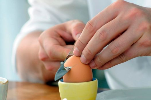 eating a breakfast egg for breakfast, opening an egg in an egg cup