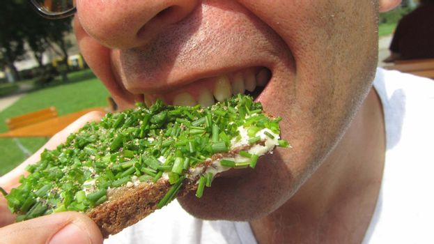 guy bites into bread with spread and chives, vegan snack
