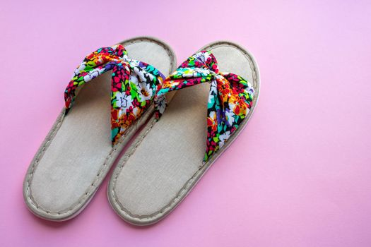 Colored home women's slippers on a pastel paper pink background. Top view. Copy space