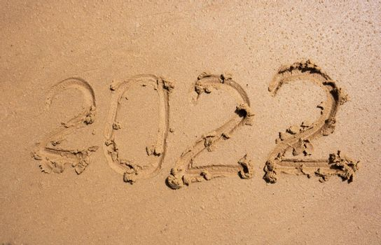 The numbers 2022 on the wet sand. The concept of the New Year 2022. Summer holidays and sea trips