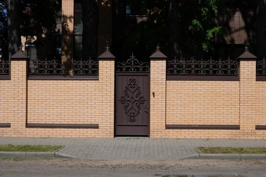 Light brown brick fence and wrought iron door next to the road