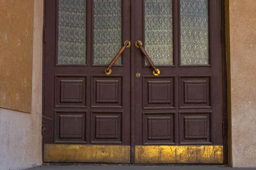 Antique door handles on a brown wooden door with fluted panes