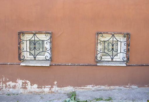 Two windows with antique bars on the plinth .Red facade with small windows
