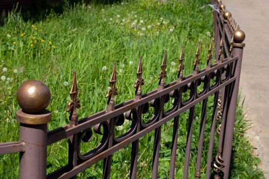 Image of a Beautiful decorative cast iron wrought fence with artistic forging. Metal guardrail close up