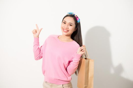 Cheerful young pretty woman raising shopping bags, dancing and looking at camera. Consumerism concept. Isolated front view on white background.