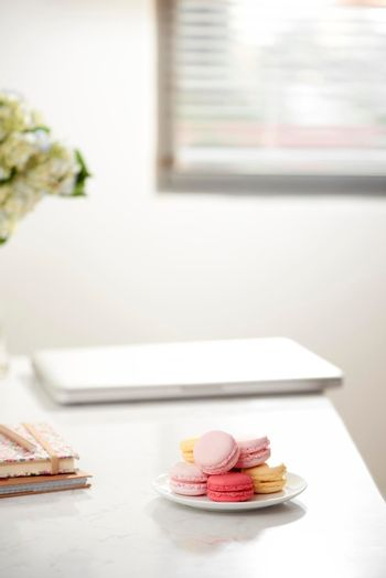 Home office desk with beautiful hortensia bouquet, macaron in front near window. Blog, website or social media concept .