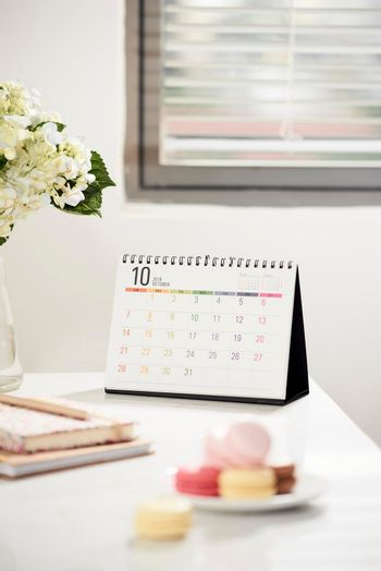 Office table desk. Feminine desk workspace frame with calendar, diary, hortensia bouquet and macaron on white background. ideas, notes or plan writing concept