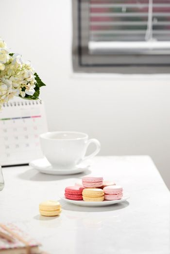 Office table desk. Feminine desk workspace frame with calendar, diary, hortensia bouquet, macaron and coffee on white background. ideas, notes or plan writing concept