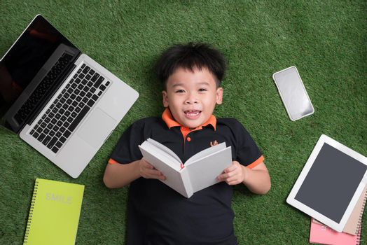 seven years old child reading a book lying on the grass