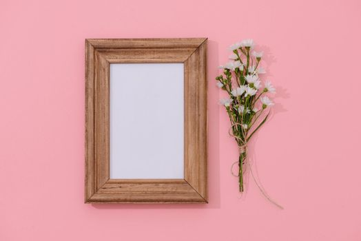 wooden frame mockup with fallen flowers in the background