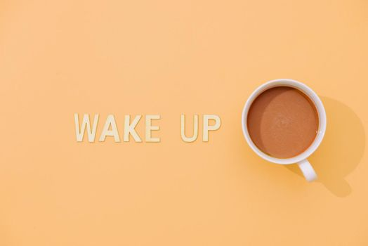WAKE UP text with a cup of coffee with shadow on pink background.
