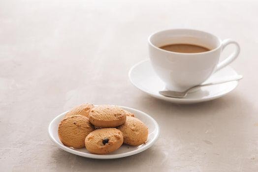 Coffee. White porcelain cup of freshly brewed coffee top view close-up arranged with  biscuits, spoon and plate on light background